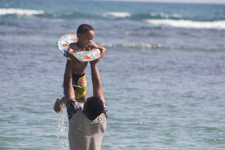 Father Carrying Son In Sea