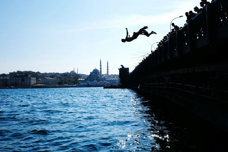 Silhouette children jumping in water at bosphorus strait against sky