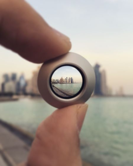 View Of River And City Seen Through Lens Held By Woman