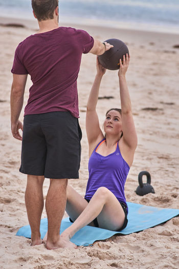 Trainer Assisting Woman Exercising With Medicine Ball At Beach