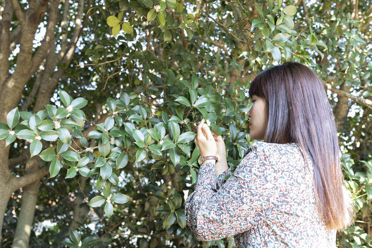 Side view of young woman standing against plants
