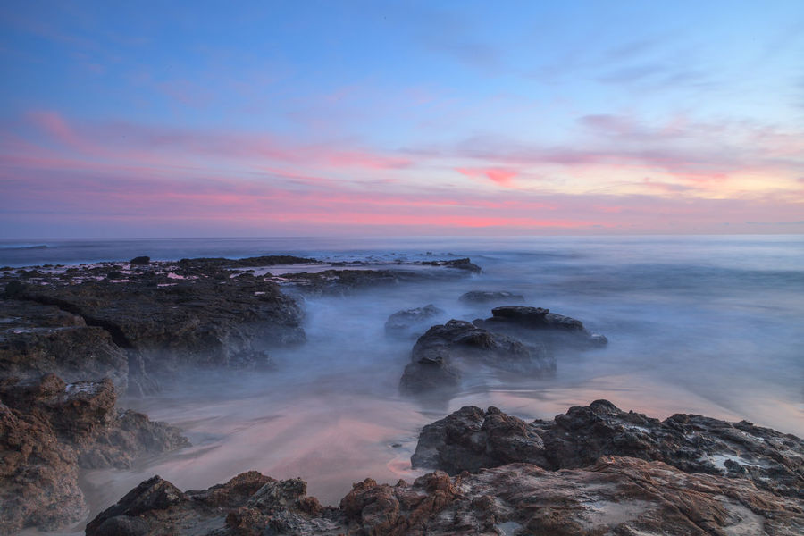 Sunset over the rocks at Shaws Cove in Laguna Beach as water flows over the stone Beach Beach Photography Beauty In Nature Coastal Coastline Landscape Horizon Over Water Horizontal Landscape Mist No People Outdoors Sea Southern California Sunset Sunsets