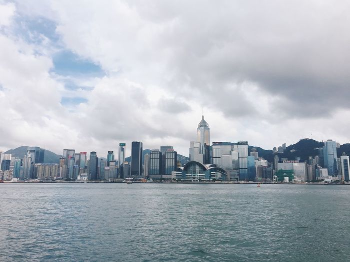 Hong kong skyline against cloudy sky
