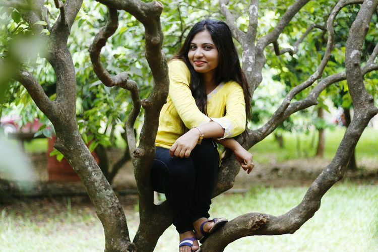 Full length portrait of young woman sitting on tree trunk