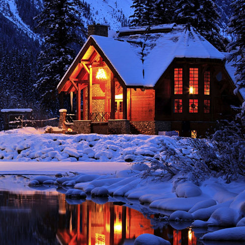Snow covered houses by building during winter at night