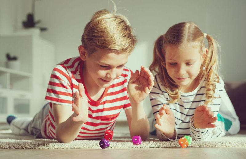 Cute sibling playing with dice on floor at home