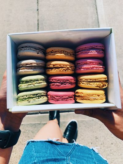Low section of woman holding macaroons in box