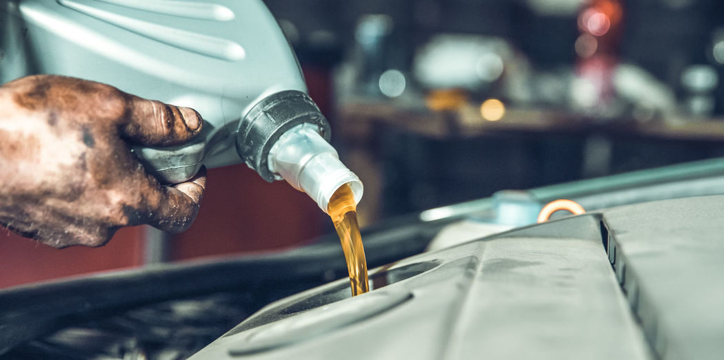 Cropped hand of mechanic pouring motor oil in vehicle