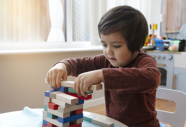Cute boy playing block removal game at home