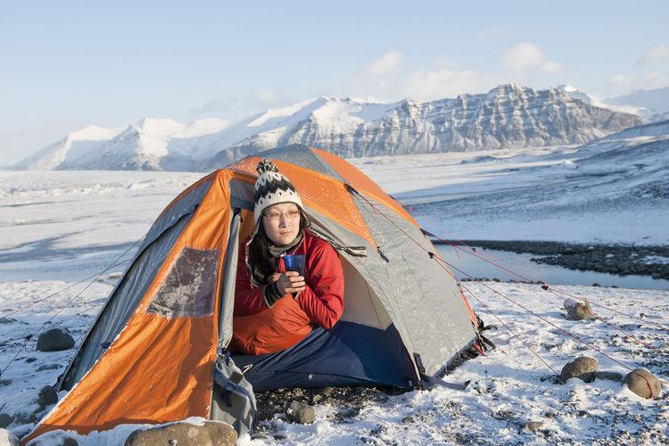 Man sitting on snowcapped mountain