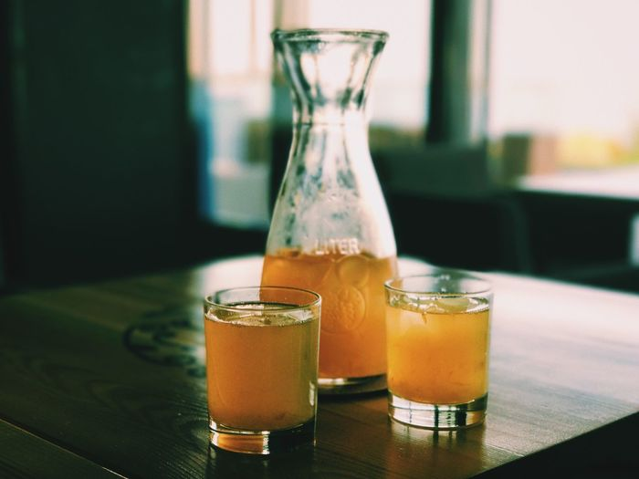 Close-up of juice in glass and container on table