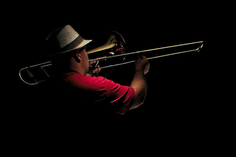 Man playing trumpet against black background