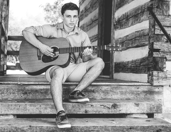 Attractive Black And White Casual Clothing Dark Hair Day Full Body Full Length Guitar Looking At Camera Male Man Monochrome One Person Outdoors Person Playing Music Portrait Serious Sitting Stairs Young Adult