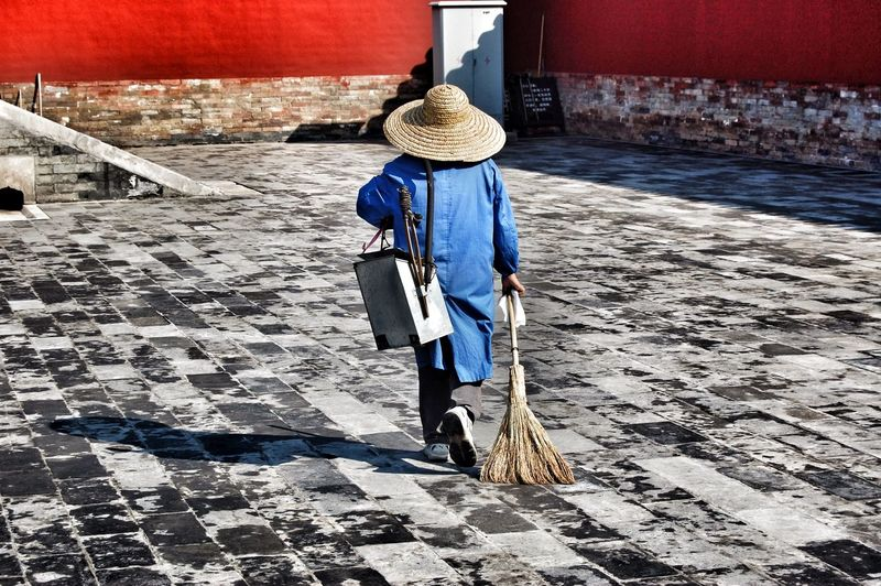 Rear view of a man holding broom