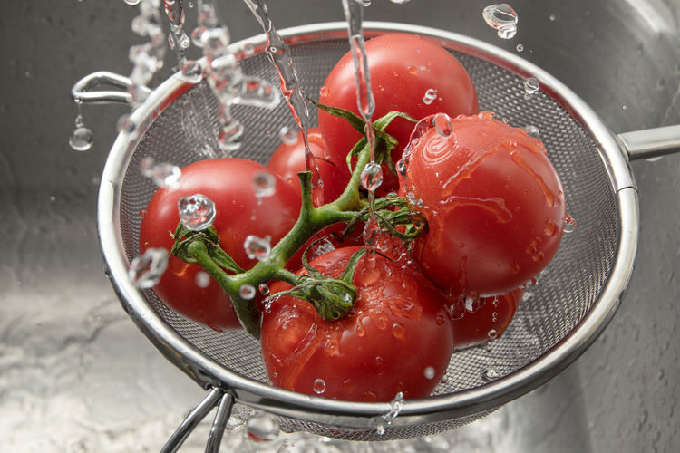 Close-up of water splashing on tomatoes in colander at sink