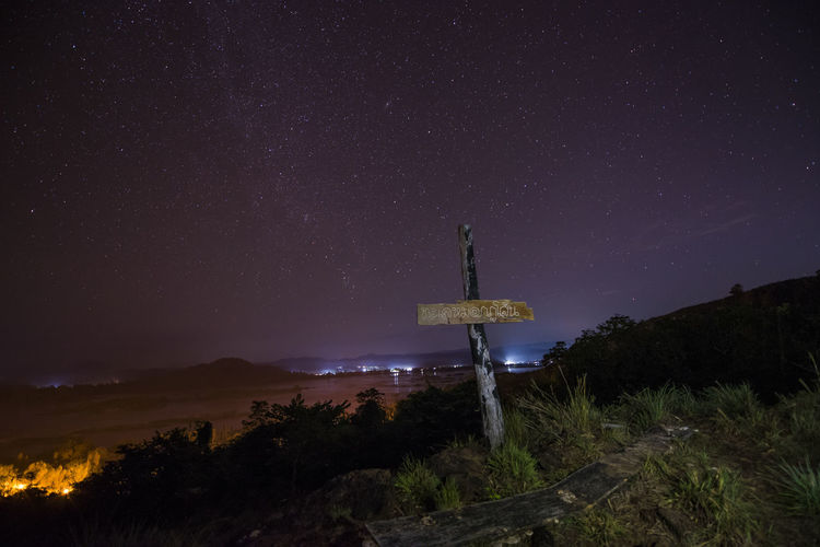 Text on wood against landscape and sky at night