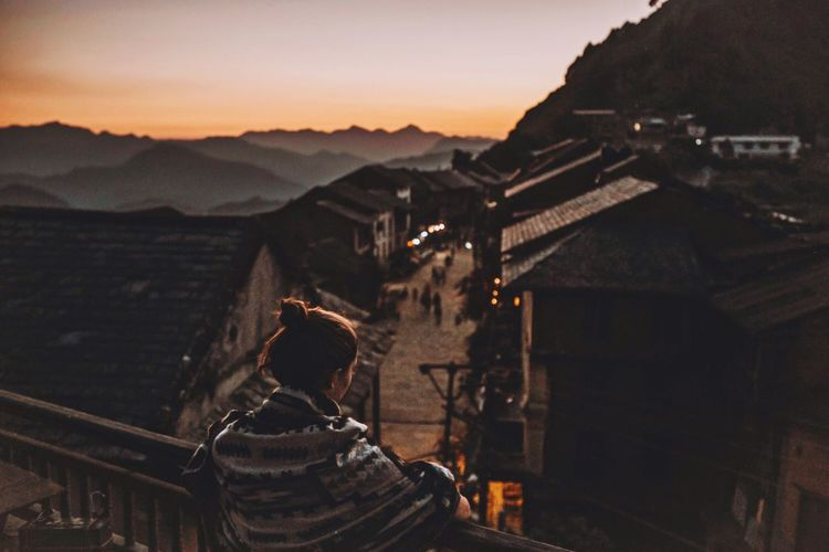 High angle view of woman standing by railing while looking at village during sunset