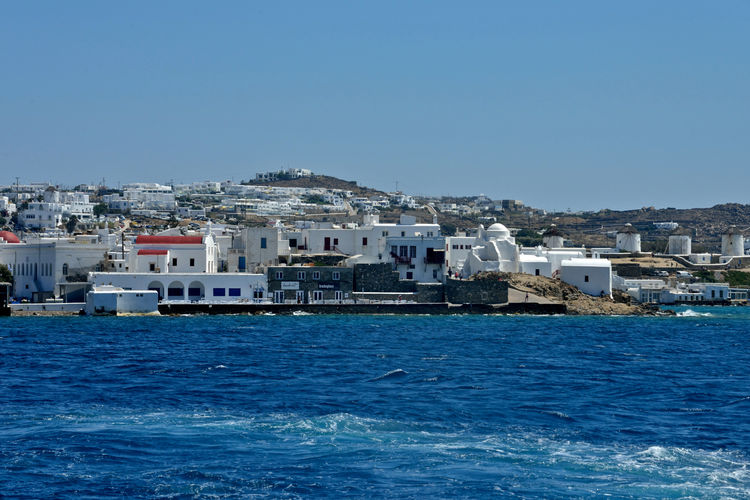 panoramic seaside view of Mykonos with white buildings Water Architecture Building Exterior Sea Sky Built Structure Waterfront Clear Sky Building Nautical Vessel Nature City Day Transportation Blue No People Copy Space Residential District Outdoors Cityscape Yacht Passenger Craft Luxury Mykonos,Greece Seaside Resort Landscape Seascape Travel Destinations White Building Greek Architecture Summertime Holiday Panoramic View Panorama