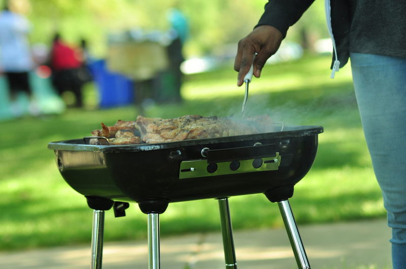Cropped Image Of Person Preparing Food On Barbeque At Park