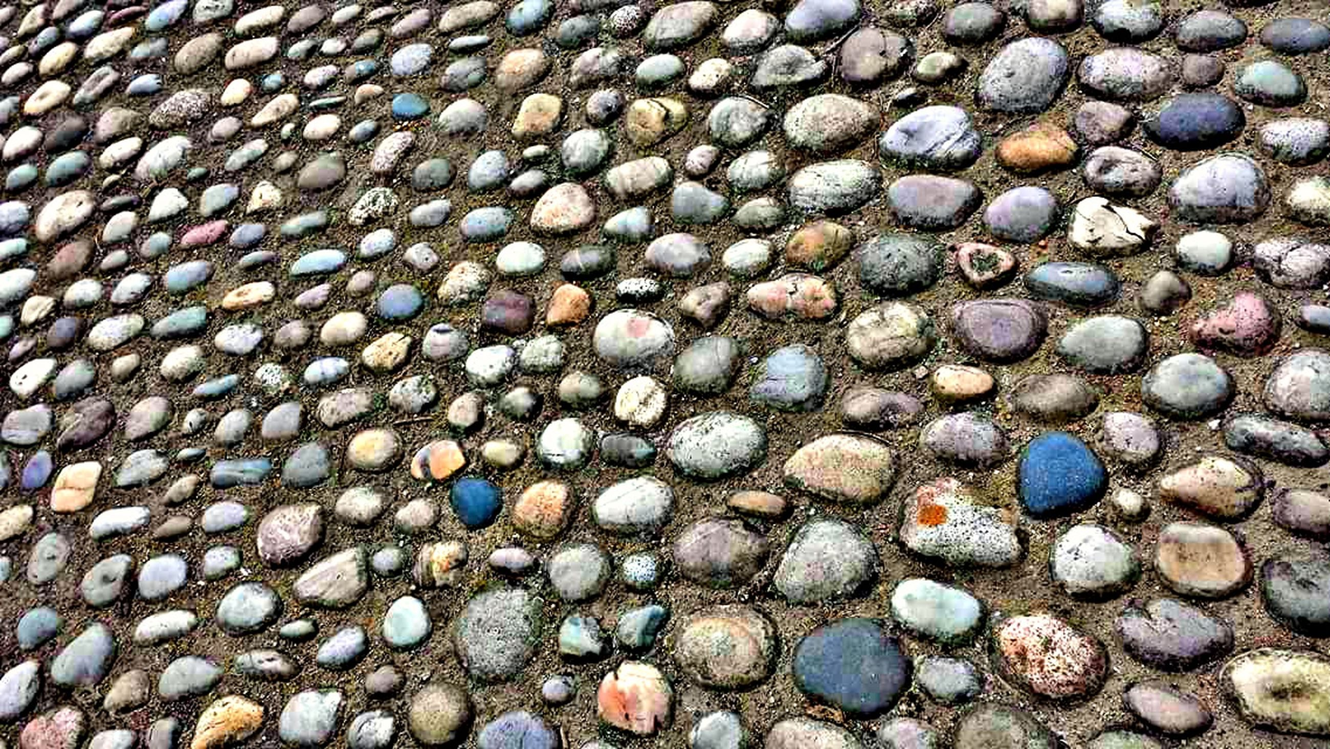 full frame, backgrounds, textured, stone - object, pebble, high angle view, close-up, day, multi colored, abundance, outdoors, stone, extreme close up, large group of objects, shore, no people, stone material, colorful, overhead view