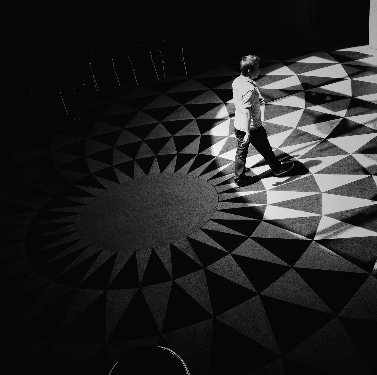 High angle view of man walking on designed flooring