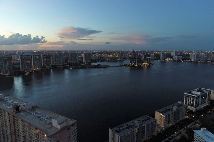 High angle view of buildings by sea against sky during sunset