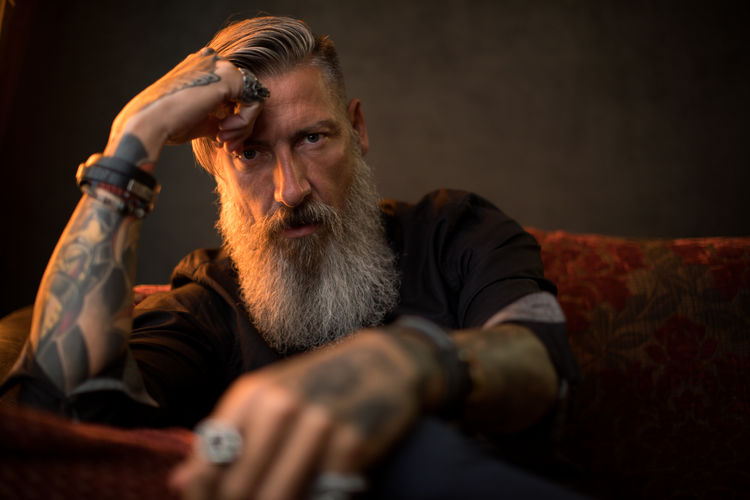 Portrait of an attractive, thoughtful modern business man in front of a dark background Tattooed Beard Bearded Black Background Boss Businessman Club Confident  Contemplation Headshot Indoors  Lifestyles Looking Looking At Camera Males  Mid Adult Millionnaire Mustache One Person Portrait Serious Sitting Successful Tattoo Thoughtful