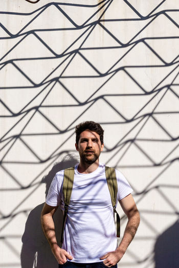 Portrait of handsome man standing by wall