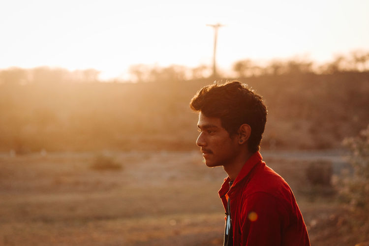 One Person Real People Lifestyles Leisure Activity Looking Away Young Men Land Young Adult Side View Looking Focus On Foreground Nature Sunset Sky Casual Clothing Field Standing Portrait Sunlight Outdoors Contemplation Profile View
