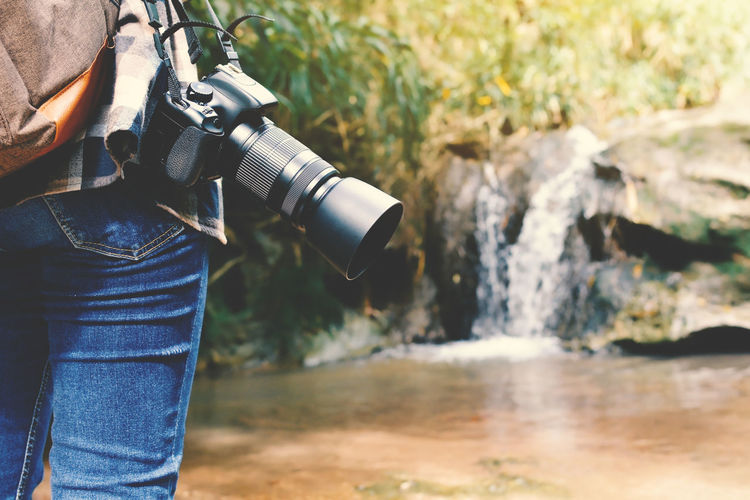 Cropped image man with camera standing by stream