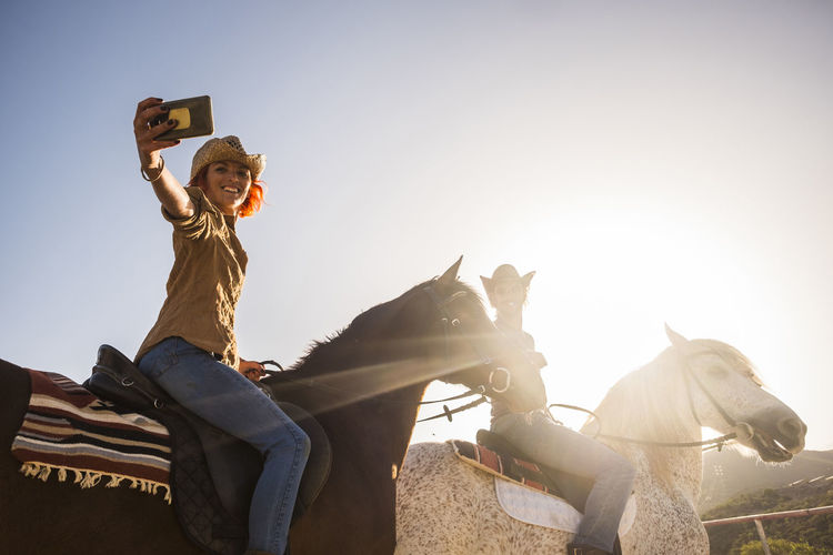 Woman Taking Selfie While Doing Horseback Riding With Friend