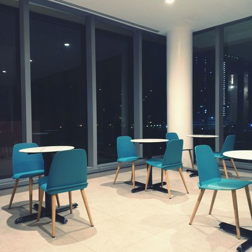 Empty chairs and tables in illuminated building