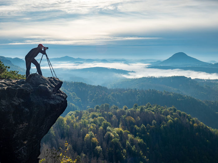 Lone nature photographer traveler take photo of beautiful morning landscape from top of the mountain