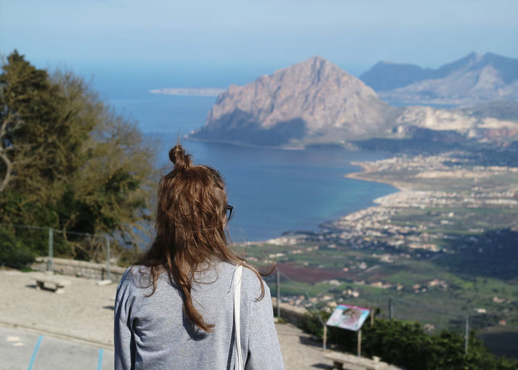 Rear view of woman with hair bun standing against mountains
