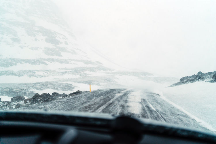 Scenic view of snowcapped mountains seen through car windshield