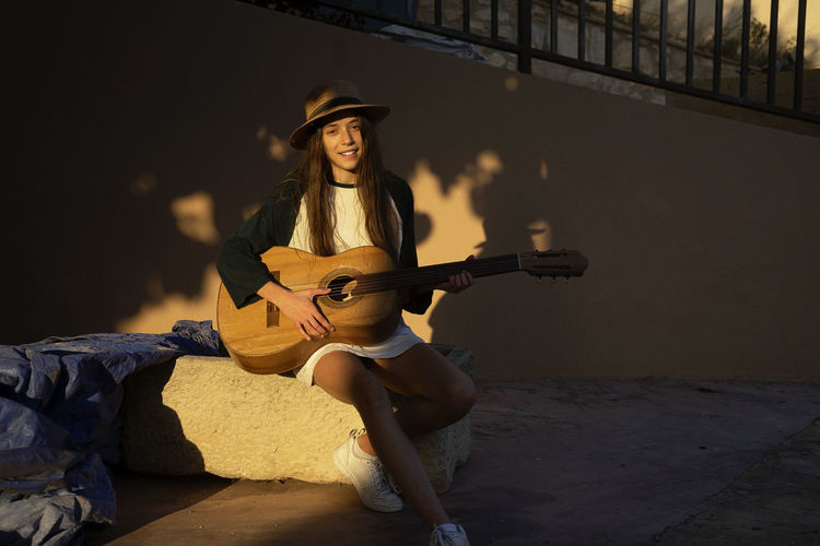 Young woman wearing hat playing guitar while sitting outdoors