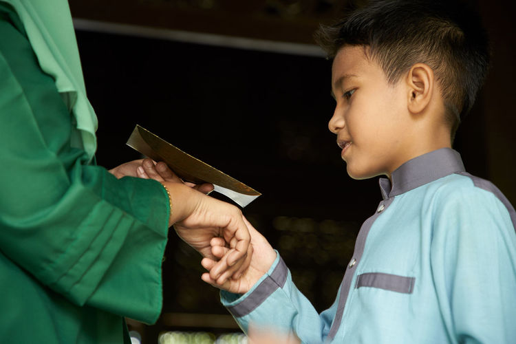 Profile view of malay son greeting and asking forgiveness to mother during ramadan festival