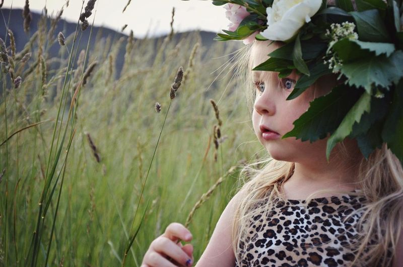 Close-Up Of Little Girl Wearing Floral Crown On Field