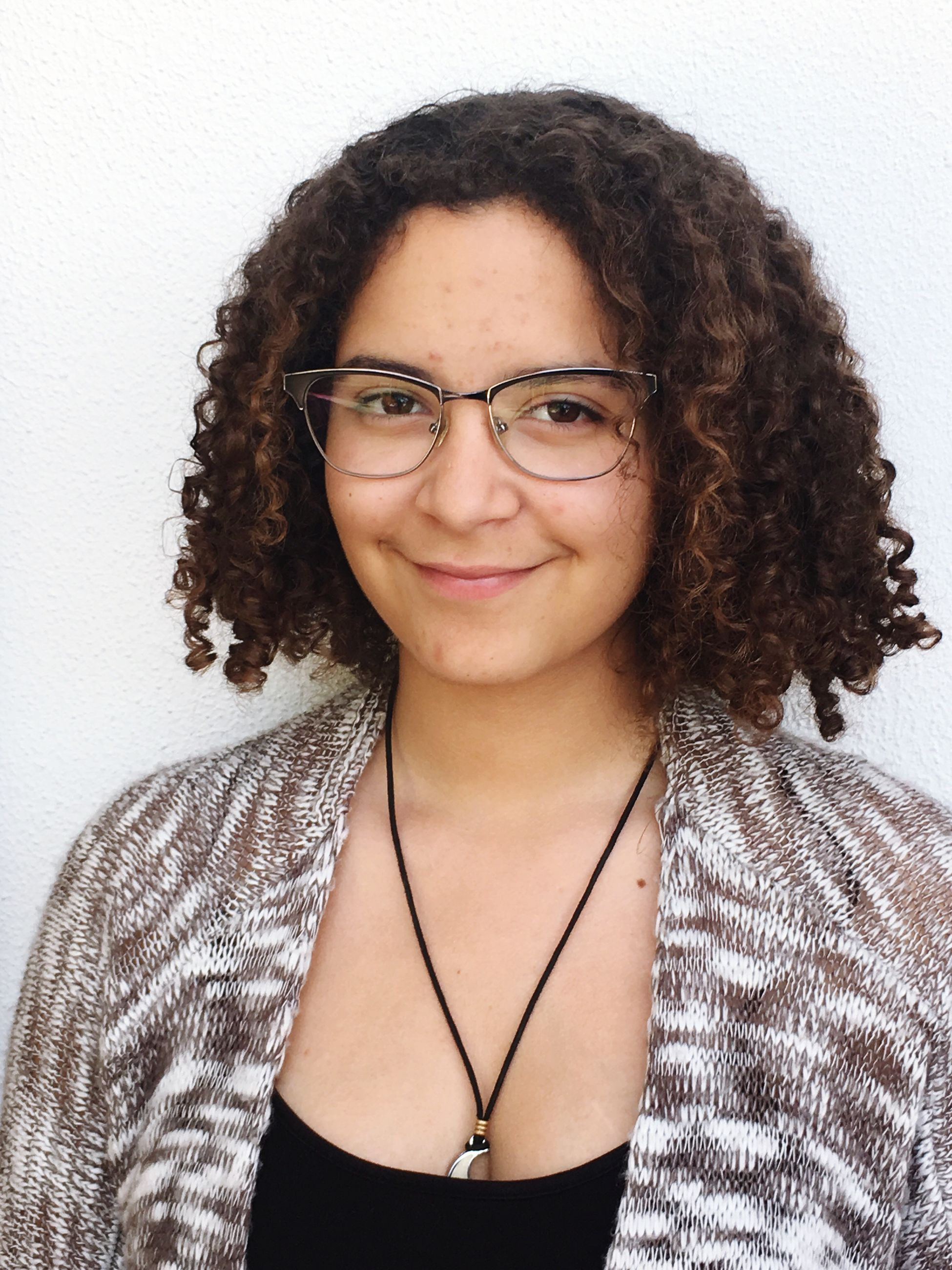 portrait, looking at camera, white background, confidence, eyeglasses, one person, young adult, one woman only, adults only, smiling, real people, people, young women, beautiful woman, adult, curly hair, one young woman only, only women, day