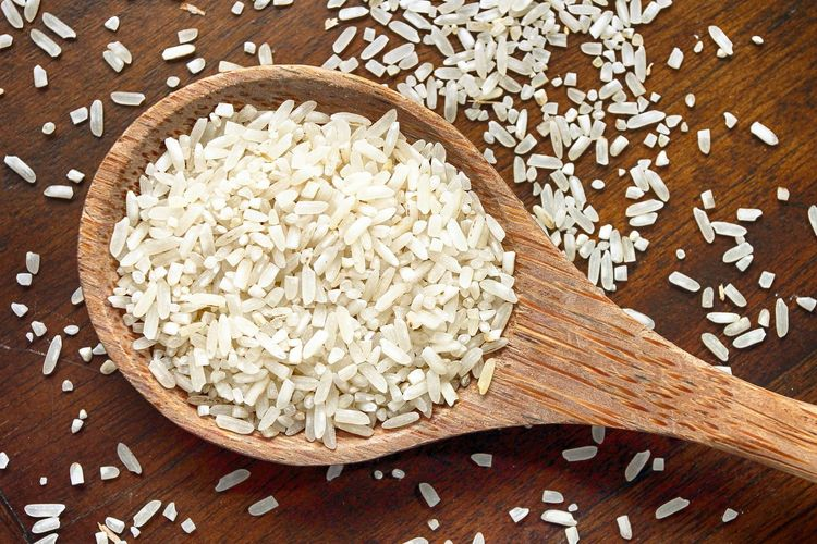 Close-up of rice in wooden spoon on table