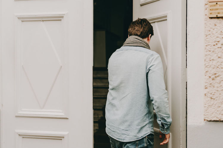 Rear view of young man entering house