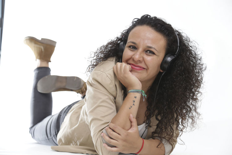 listening music with headphones, enjoying music Headphones Adult Curly Hair Emotion Females Front View Hair Hairstyle Happiness Indoors  Leisure Activity Long Hair Looking At Camera Mature Women Music Time One Person Portrait Real People Smiling Women Young Women