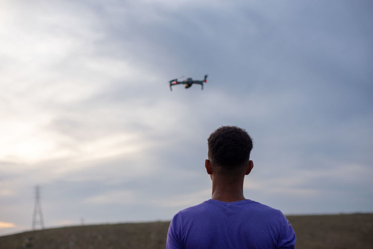 Rear view of man with airplane flying against sky