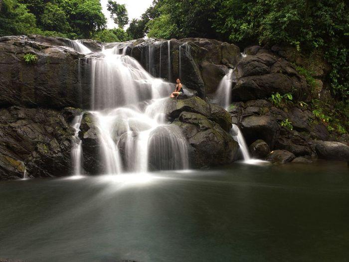 Woman sitting by waterfall on rocks