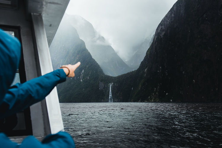 Woman Pointing Towards Waterfall And Mountains