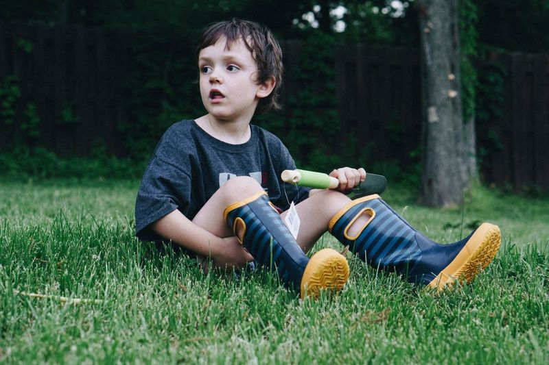 Full length of boy looking away while sitting on grassy field