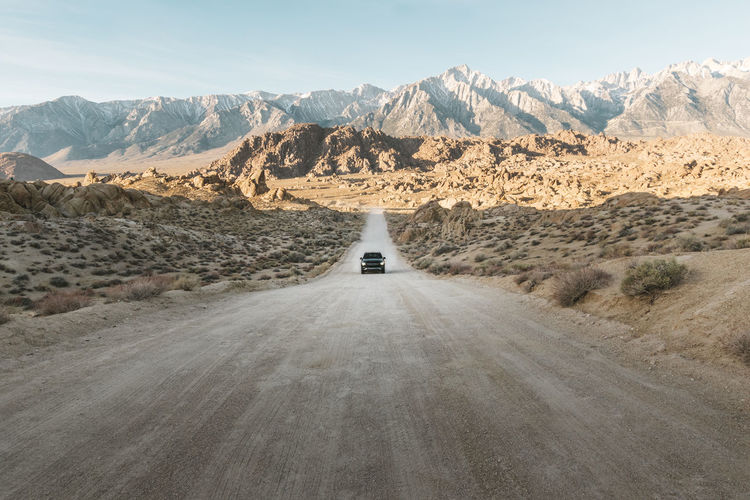 Car on dirt road leading towards mountains