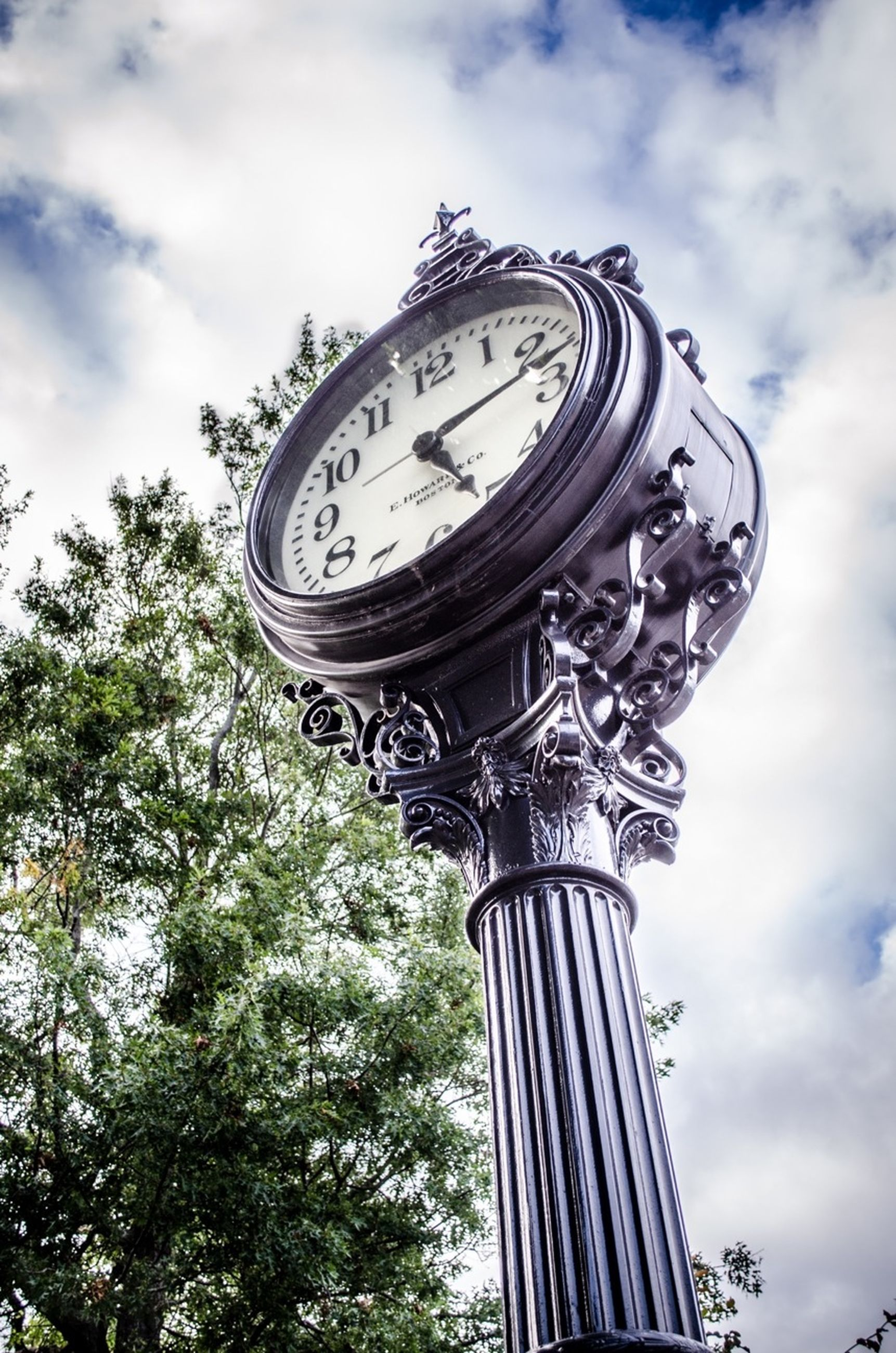 low angle view, sky, clock, time, text, cloud - sky, tree, cloud, history, architecture, communication, built structure, day, ornate, famous place, travel destinations, art and craft, no people, religion, cloudy