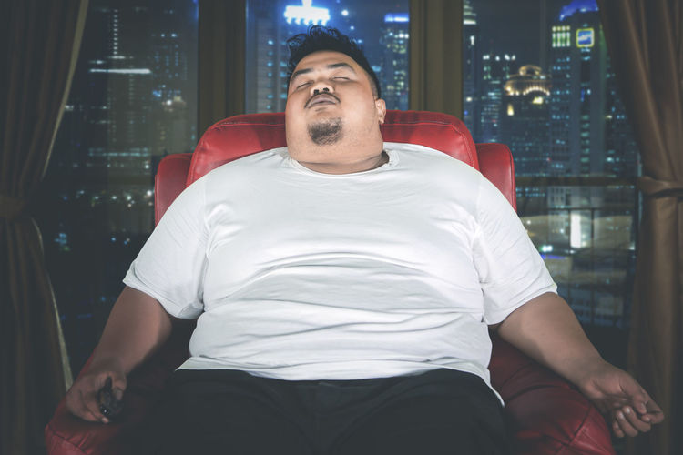 Lazy overweight young man sleeping on sofa at home during night