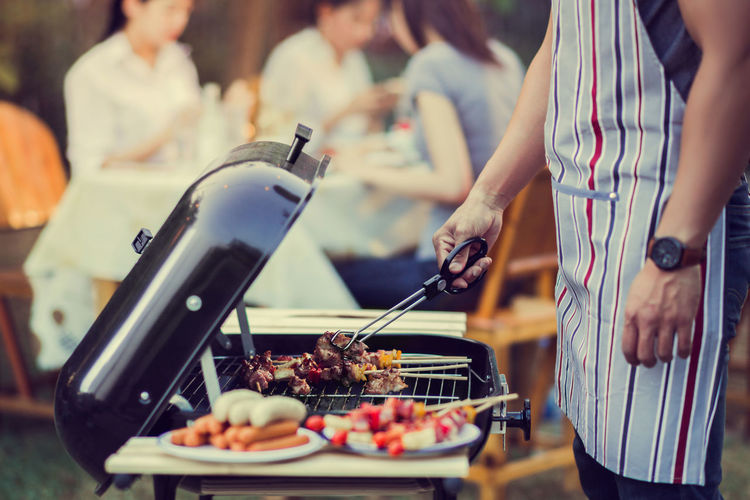 Barbecue Focus On Foreground Food Food And Drink Freshness Group Of People Hand Healthy Eating Holding Incidental People Leisure Activity Lifestyles Meat Men Midsection People Preparation  Preparing Food Real People Selective Focus Standing